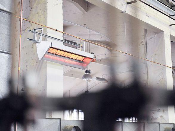 Ein Hellstrahler der Firma Schwank in Betrieb an der Wand einer Halle.